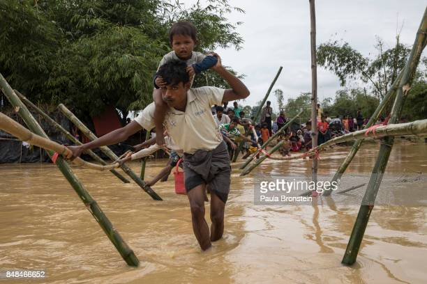 Refugees balance on bamboo as they try and cross a stream as the monsoon rains create challenges for the displaced Rohingya September 17 2017 in...