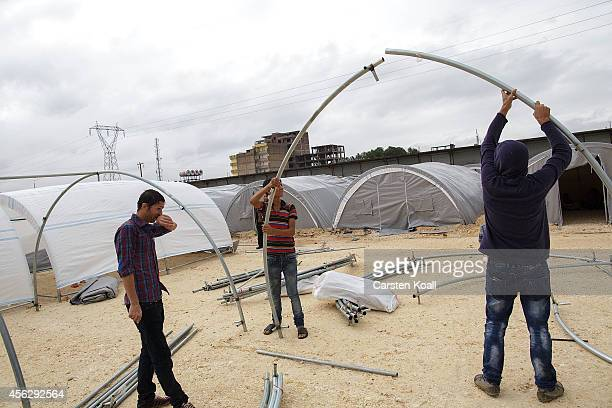 Refugees build new tents in a refugee camp after crossing from Syria into Turkey in Suruc September 28 2014 south of Sanliurfa Turkey Islamic State...