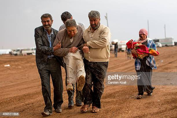 Refugees carry an old man in heavy rain who had arrived from Syria at the border crossing on October 2 2014 near Suruc Turkey The Turkish Parliament...