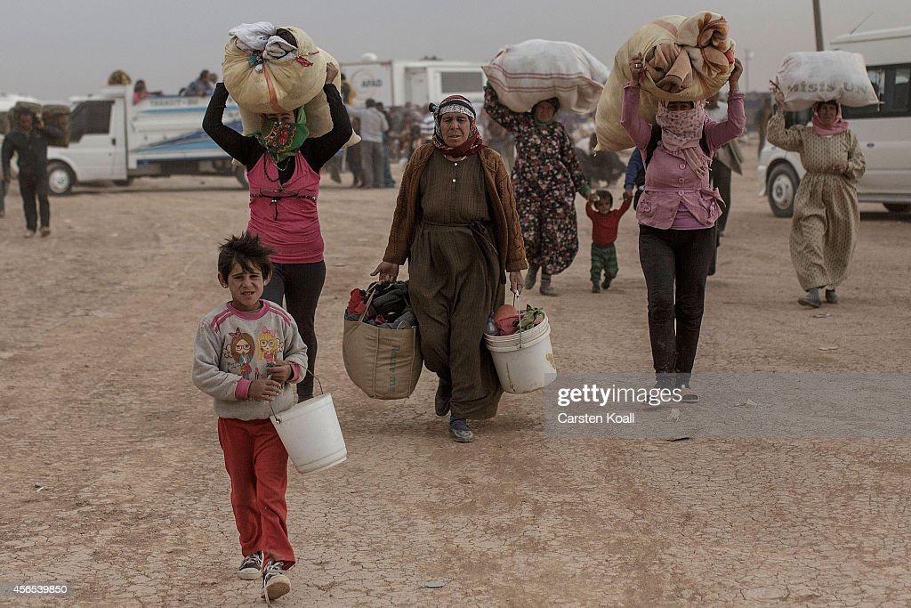 Refugees carry some belongings while crossing the border