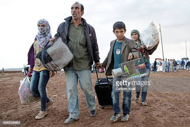 Refugees carry some belongings while crossing the border from Syria into Turkey on October 2 2014 near Suruc Turkey The Turkish Parliament is...