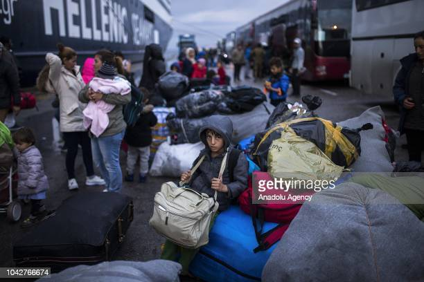 Refugees carry their belongings after the discharge actions were started in the Moria refugee camp of Lesbos which draws reaction due to the poor...