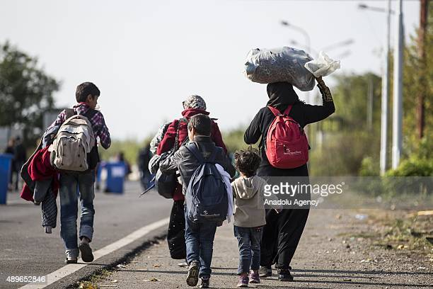 Refugees carry their belongings as they walk towards the Austrian border from Hegyeshalom on September 23 2015