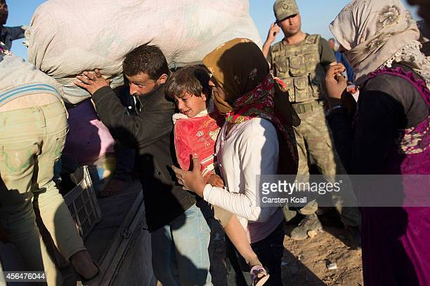 Refugees carry their belongings to a truck after crossing the border from Syria into Turkey on October 1 2014 near Suruc Turkey Kurdish troops are...