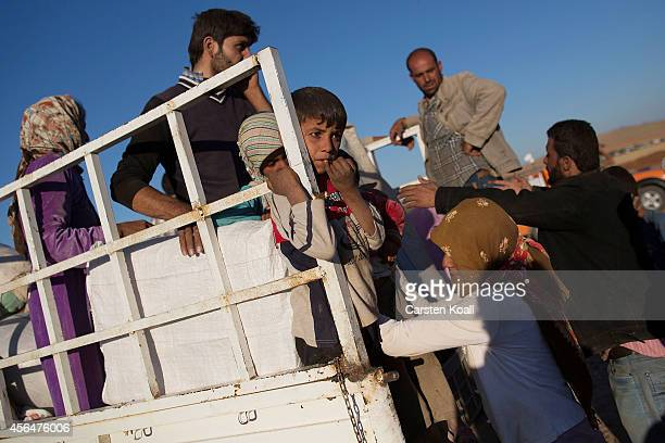 Refugees climb onto a truck to sit to be transported away after crossing the border from Syria into Turkey on October 1 2014 near Suruc Turkey...