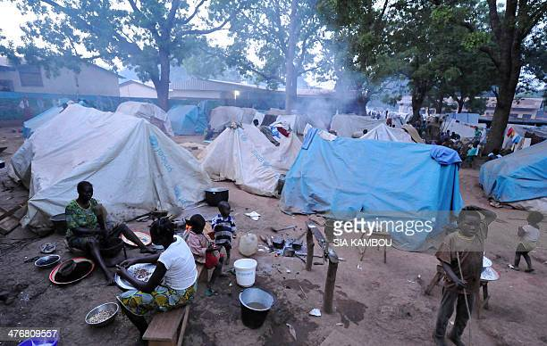 Refugees cook outside their tent in a camp set up within the vicinity of the Catholic church of Bossangoa on March 5 2014 United Nations diplomats...