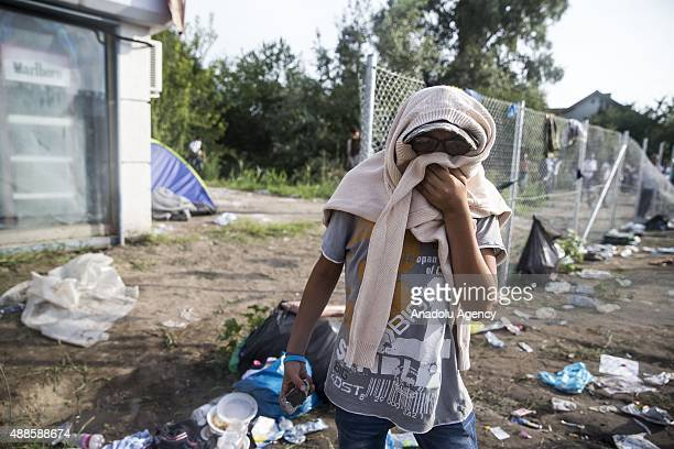 Refugees cover their faces as they ran away from tear gas during a clash with Hungarian riot police at the Horgos border near the town of Kanjiza...