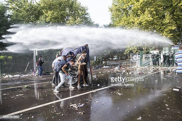 Refugees cover themselves with a tent as they ran away from tear gas during a clash with Hungarian riot police at the Horgos border near the town of...