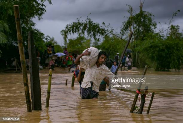 COX'S BAZAR BANGLADESH SEPTEMBER 19 Refugees cross a flooded bridge in the Balukhali Rohingya refugee camp on September 19 2017 in Cox's Bazar...