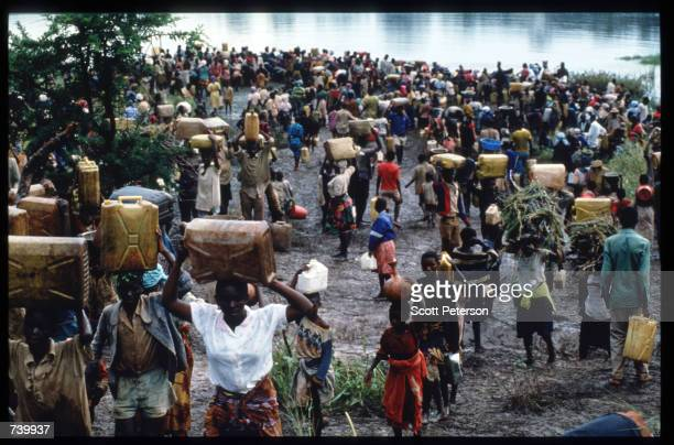 Refugees crowd along the banks of a river May 3 1994 at the border of Rwanda and Tanzania Hutu refugees have fled to Tanzania across the Akagara...
