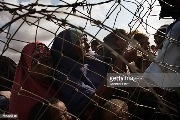 Refugees desperate to move to a less crowded refugee camp stand behind a United Nations fence in Dadaab, the world�s biggest refugee complex August...