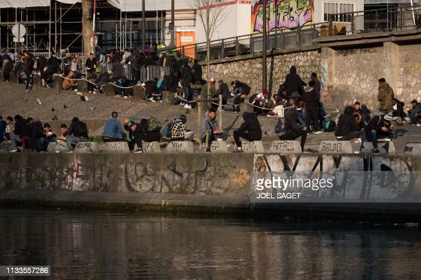 Refugees eat a meal distributed by an association on March 29 2019 in Paris
