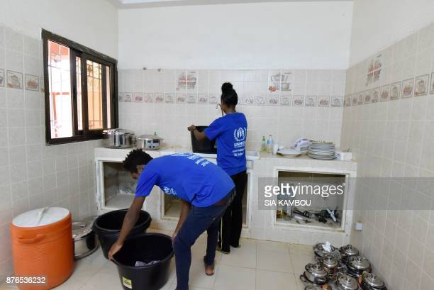 Refugees fill buckets with water with which they will wash clothes in the kitchen at a UNHCR building in Niamey on November 17 after they were...