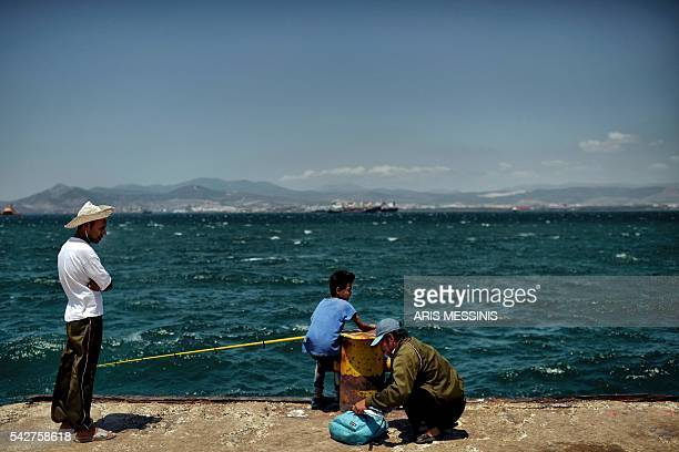 Refugees fish in the sea next to the refugee camp of Skaramangas in Athens on June 24 2016 Over 800000 migrants fleeing war persecution and hardship...