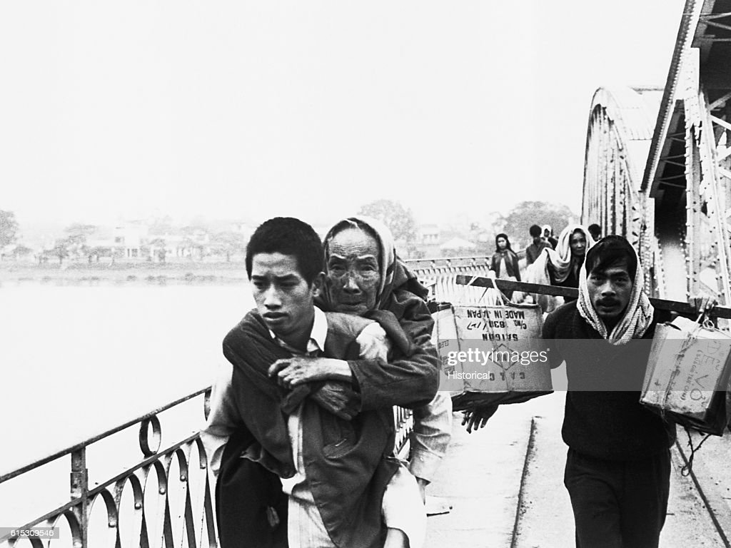 Refugees flee across this bridge over the Perfume River to escape Tet fighting in Hue. The bridge was soon dropped into the river by the Communists. Vietnam, 1968.