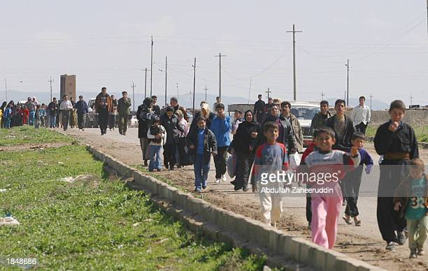 Refugees flee from the city of Kirkuk as they head towards an Iraqi Kurd area known as Khush tapa March 14, 2003 which is located south of Erbil in...