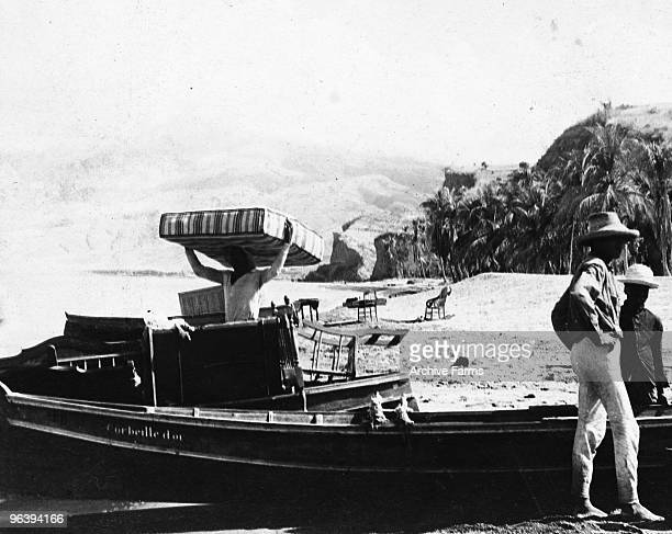 Refugees fleeing after the eruption of the Mount Pelee volcano load furniture on boats on May 10 1902 at St Pierre Martinique