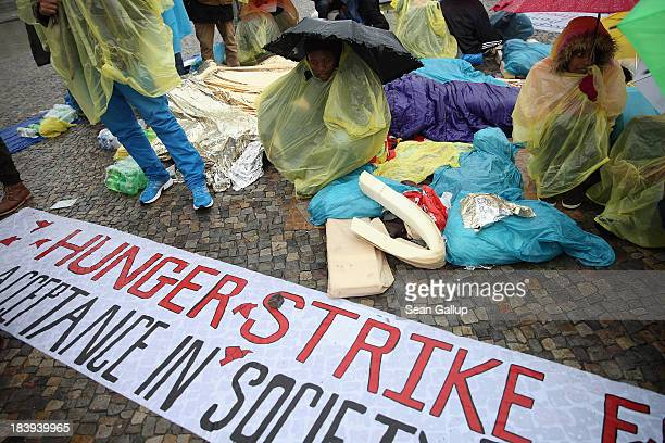 Refugees from Congo and Ethiopia huddle under rain on the second day of a hunger strike in front of the Brandenburg Gate on October 10 2013 in Berlin...