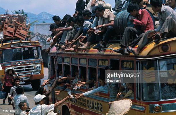 Refugees from Da Nang Hue and other fallen South Vietnam cities crowded with their belongings aboard buses reach out for food and water as they head...