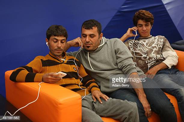 Refugees from Iraq listen to music on headphones in an airdome used as a temporary shelter for refugees on September 26 2015 in Berlin Germany...
