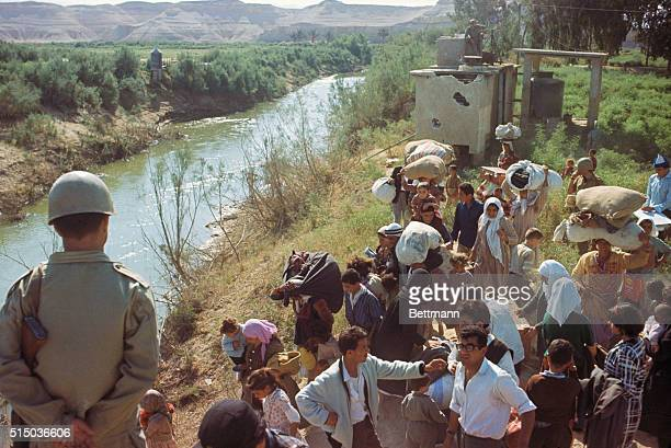 Refugees from Israeli occupied Jordan crossing the river Jordan at wrecked Allenby Bridge, where timber has been used to patch up the bridge as a...