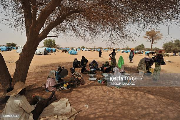Refugees from northern Mali sit under a tree inside UNHCR Mangaize refugee camp 145 km north of Niamey on June 2 2012 Rebel Tuareg and Islamist...