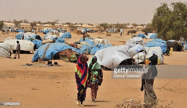 Refugees from northern Mali walk beside makeshift shelters at the UNHCR Mangaize refugee camp 145 km north of Niamey on June 2 2012 Rebel Tuareg and...