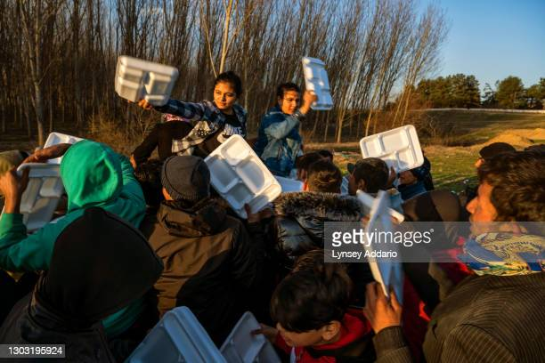 Refugees from Syria, Afghanistan, Iraq, Iran, and other countries scramble to get a hot meal being handed out by a local Turkish family at the...