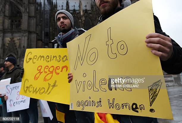 Refugees from Syria hold a sign reading 'No to violence against women' as they demonstrate against violence at the Cologne main train station in...