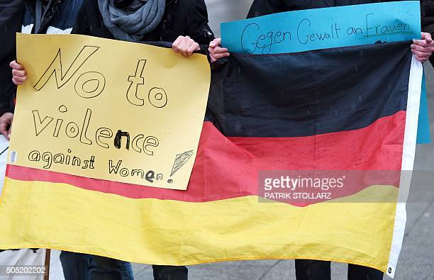 Refugees from Syria hold a sign reading 'No to violence against women' with a German flag as they demonstrate against violence at the Cologne main...