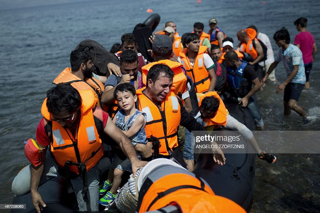 Refugees from Syria land on the shores of the Greek island of Lesbos aboard an inflatable dinghy across the Aegean Sea from from Turkey on September 7, 2015. Greece sent troops and police reinforcements September 6 to Lesbos after renewed clashes between police and migrants, the public broadcaster said, while Syrian refugees on the island were targeted with Molotov cocktail attacks. More than 230,000 people have landed on Greek shores this year and the numbers have soared in recent weeks as people seek to take advantage of the calm summer weather.