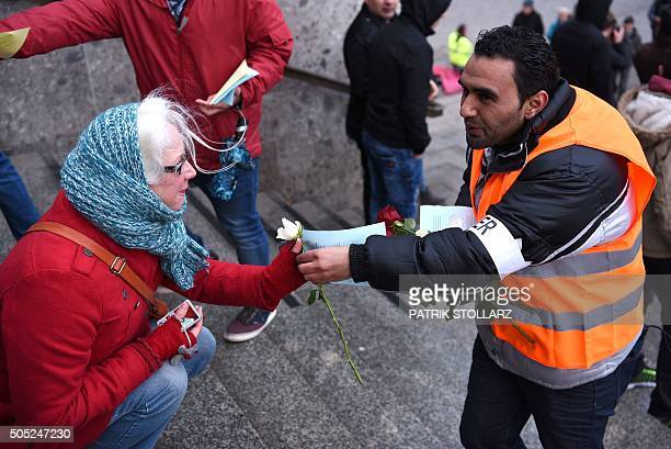Refugees from Syria present flowers to passers-by as they demonstrate against violence near the Cologne main train station in Cologne, western...