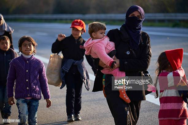 Refugees from Syria walk along the highway towards the border with Macedonia where refugees and migrants remain stuck on February 25 2016 in Idomeni...