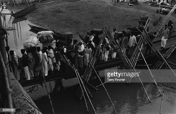 Refugees from Tezpur India crossing a wooden bridge during the IndiaPakistan conflict
