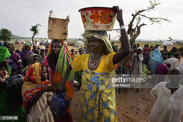Refugees from the Darfur region of Sudan line up for water at a spontaneous overflow camp August 27 2004 outside the Bredjing camp in Chad More than...