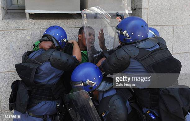 Refugees from the Democratic Republic of Congo clash with police as they stage a protest outside the French Embassy on December 6 2011 in Cape Town...