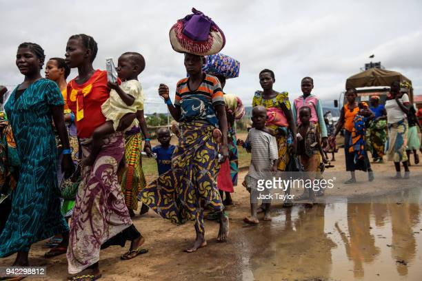 Refugees from the Democratic Republic of Congo make their way on to a bus for the Kagoma reception centre from the UNHCR landing site for refugee...