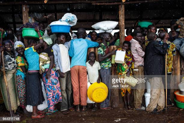 Refugees from the Democratic Republic of Congo stand under a shelter with their food collected from the World Food Programme as it rains in the...