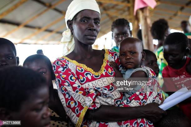 Refugees from the Democratic Republic of Congo wait with their children to be screened for malnourishment in the Kyangwali Refugee Settlement on...