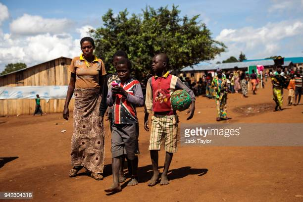 Refugees from the Democratic Republic of Congo walk through the Kagoma reception centre on April 5 2018 in Kyangwali Uganda According to the UNHCR...