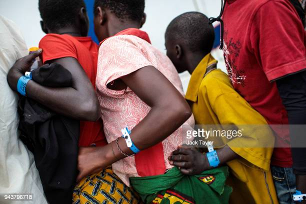 Refugees from the Democratic Republic of Congo wearing registration wristbands prepare to board a bus from the Nsonga landing site to a reception...