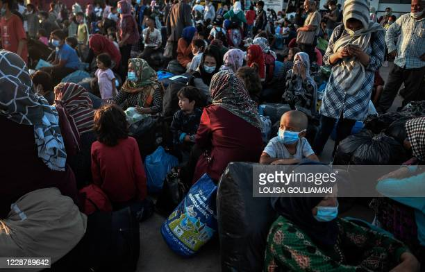 Refugees from the islands of Lesbos, Chios, Samos, Kos and Leros wait to board buses after disembarking at the port of Lavrio, some 70 km south-east...