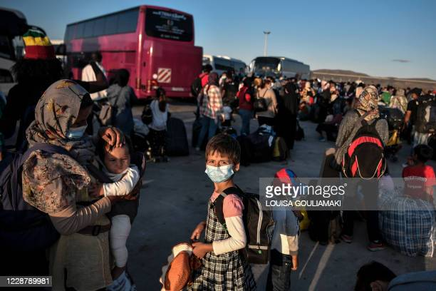 Refugees from the islands of Lesbos, Chios, Samos , Kos and Leros wait to board buses after disembarking at the port of Lavrio, some 70 km south-east...