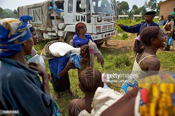 Refugees from the war in Congo share meal during a food distribution in camp Butembo for displaced persons on January 14 2013 in Goma Democratic...