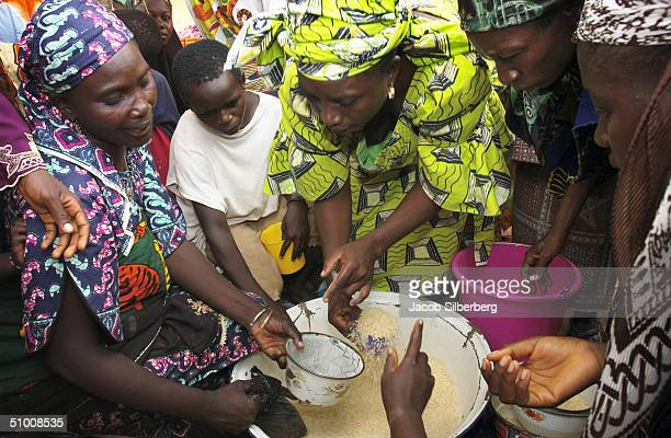 Refugees from Yelwa fight over the distribution of food donated by a Muslim charity in the Lafia refugee camp in central Nigeria May 26 2004 Farmers...