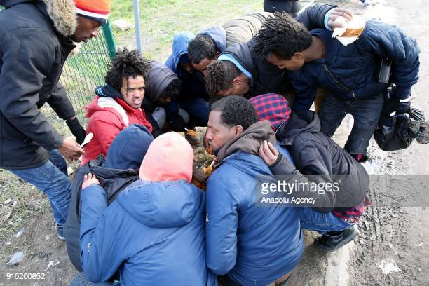 Refugees gather around a fire and eat food on a cold day after the dismantlement of Calais Jungle refugee camp in Calais in northern France on...