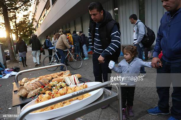 Refugees gather around food donated by a caterer outside the LaGeSo State Office for Health and Social Services the office for registering migrants...