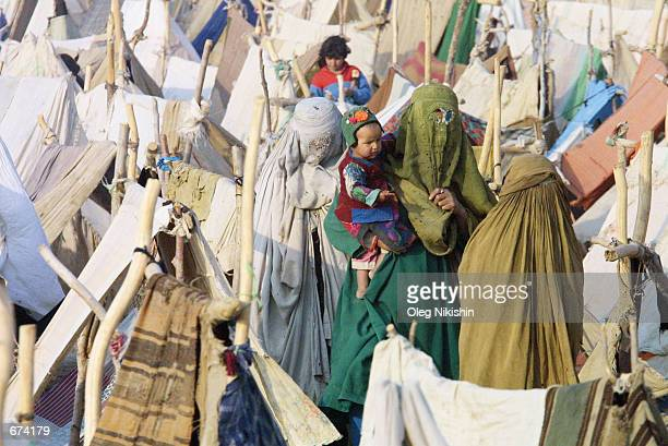 Refugees gather at a camp site at MazareSharif November 29 2001 in Afghanistan The camp has been set up to accommodate refugees from various regions...