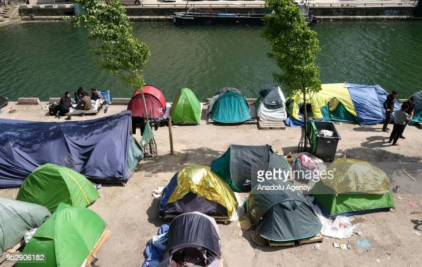Refugees gather at their makeshift camp around the Canal SaintMartin in Paris France on April 30 2018