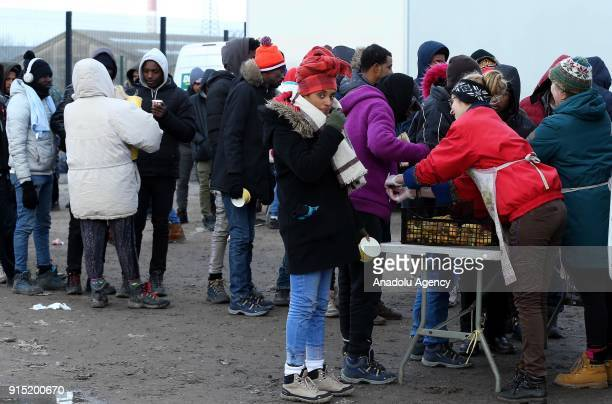 Refugees gather to eat food on a cold day after the dismantlement of Calais Jungle refugee camp in Calais in northern France on February 07 2018...